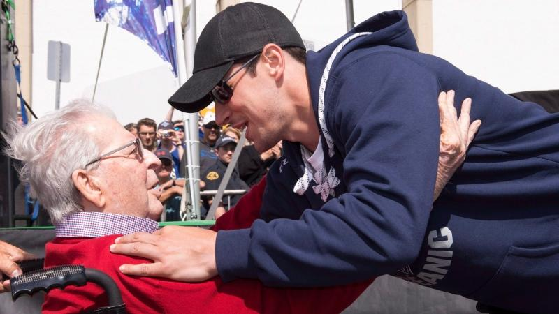 Pittsburgh Penguins Sidney Crosby hugs former Rimouski Oceanic owner Maurice Tanguay at a parade in Rimouski Que. Crosby, who played his junior career with the Oceanic in Rimouski, came with the Cup on his 30th birthday. Tanguay died Feb. 25, 2021. THE CANADIAN PRESS/Jacques Boissinot
