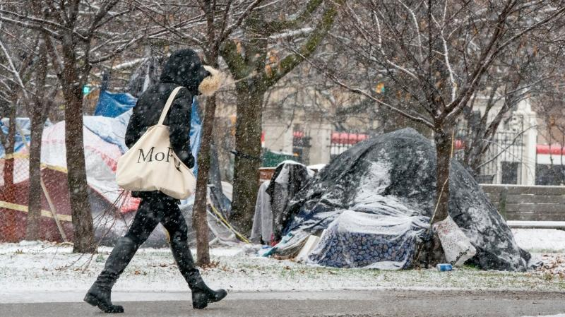 A pedestrian walks past a snow covered tent encampment in Trinity Bellwoods park in Toronto on Sunday November 22, 2020. THE CANADIAN PRESS/Frank Gunn