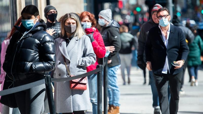 People wear face masks as they wait to enter a store in Montreal, Friday, April 2, 2021, as the COVID-19 pandemic continues in Canada and around the world. THE CANADIAN PRESS/Graham Hughes