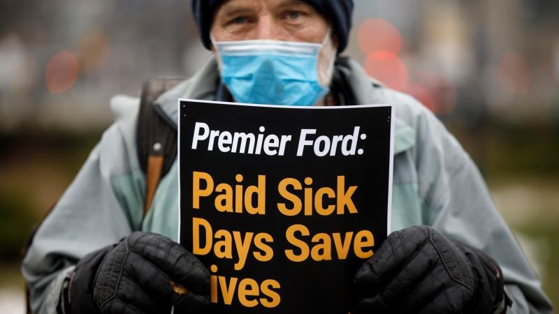 A man holds up a sign as a group advocating for Provincially mandated paid sick days for workers participates in a 'die-in' rally outside Queens Park in Toronto, Wednesday, Jan. 13, 2021. THE CANADIAN PRESS/Cole Burston