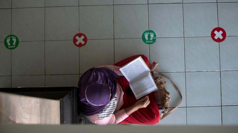 A woman reads the Quran at a mosque amid physical distancing markings while waiting for the time to break her fast during the first day of Ramadan in Bali, Indonesia on April 13, 2021. (Firdia Lisnawati / AP)