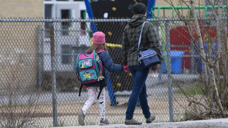 A woman walks her daughter to school Monday May 11, 2020 in Gatineau, Quebec. Quebec primary school students outside of Montreal returned to class across the province THE CANADIAN PRESS/Adrian Wyld