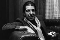8th January 1980: Solemn Canadian folk pop singer-songwriter Leonard Cohen shares a joke and smokes a cigarette.