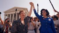 In this Wednesday, April 26, 1989 file photo, Norma McCorvey, Jane Roe in the 1973 court case, left, and her attorney Gloria Allred hold hands as they leave the Supreme Court building in Washington after sitting in while the court listened to arguments in a Missouri abortion case.