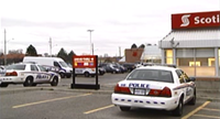 In this file photo at the same bank where a robbery occurred Saturday, April 15, 2017, police cruisers park outside the Scotiabank at Southdale Road East and Montgomery Road in London, Ont, following a robbery in November of 2015.