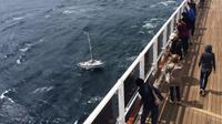 Passengers aboard the cruise liner Queen Mary 2 look on as they approach a British sailor on a disabled yacht in the Atlantic Ocean on Saturday, June 10, 2017.THE CANADIAN PRESS/HO, Dave Ashley via CTV Atlantic