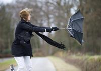 Woman holds onto an umbrella on a windy day.