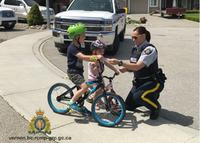 Photo: Easton and Blake DeGroot of Coldstream receiving their positive tickets from Cst. Brett for wearing their bike helmets).