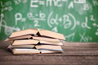 school books, math books on a desk, math on a chalkboard