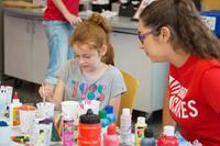 Brock student Evelyn Miloud, right, paints with a young visitor at a children's fun station set up on campus as part of Brock Cares Day of Service.