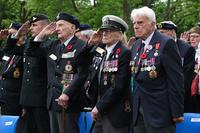 REVIERS, FRANCE - JUNE 05: Canadian veterans of the World War II Battle of Normandy and family members stand during a commemorative ceremony at the Commonwealth War Graves Commission's Beny-sur-Mer Canadian War Cemetery in Normandy on June 05, 2019 near Reviers, France. About 38 Canadian veterans took part in the ceremony at the cemetery that contains the graves of approximately 2,000 Canadian soldiers killed during D-Day and the subsequent fighting and is one of several scattered across Normandy. Veterans, families, visitors and military personnel are gathering in Normandy to commemorate the June 6, 75th anniversary of the Allied D-Day invasion, which heralded the Allied advance towards Germany and victory about 11 months later. (Photo by Sean Gallup/Getty Images)