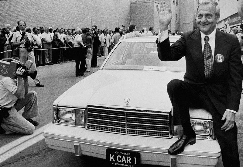 Lee Iacocca sits on the hood of K Car Number One, 1980