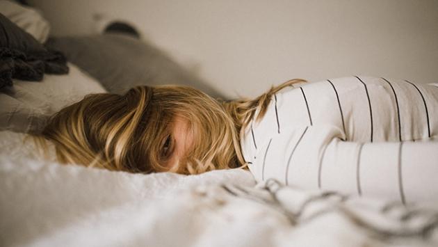 Une femme couchée face sur son lit