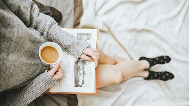 Femme qui lit un livre et qui boit un café