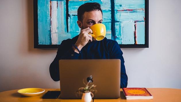 Homme qui boit un café devant son ordinateur