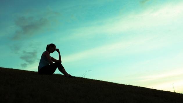 Jeune fille sur une montagne devant un ciel turquoise