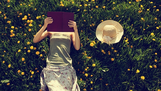 Jeune femme qui lit couchée dans l'herbe en été